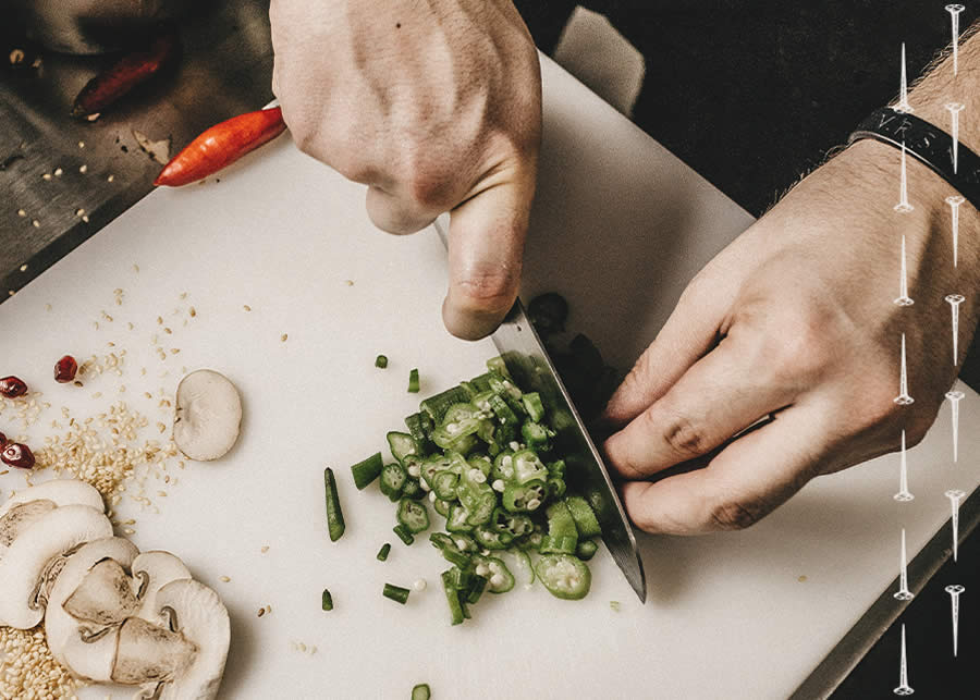 chef hands chopping vegetables on a cutting board.