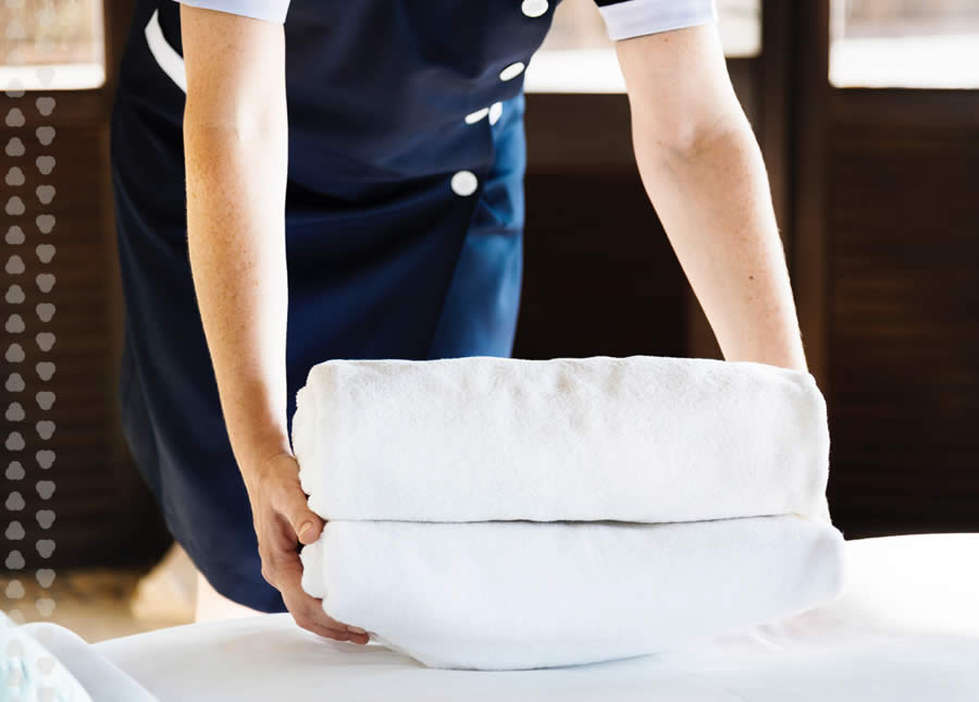 woman from housekeeping staff setting towels down one bed.