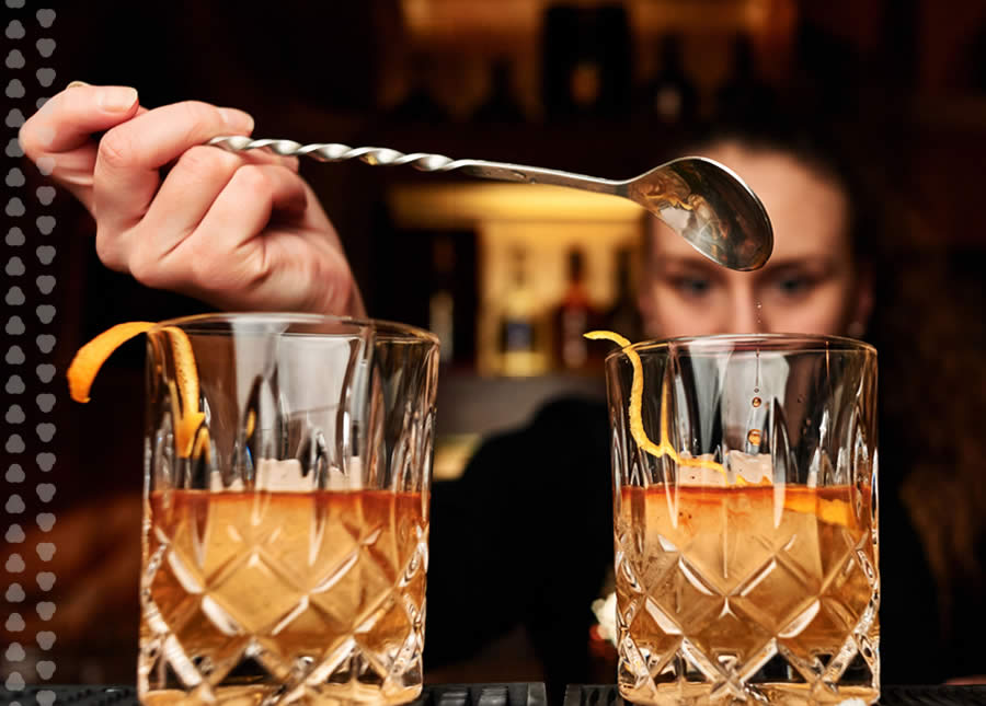 bartender spooning simple syrup into two bourbon cocktails.
