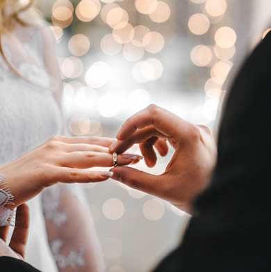 groom placing ring on bride's finger.