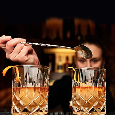 bartender mixing two bourbon cocktails in a dark bar.