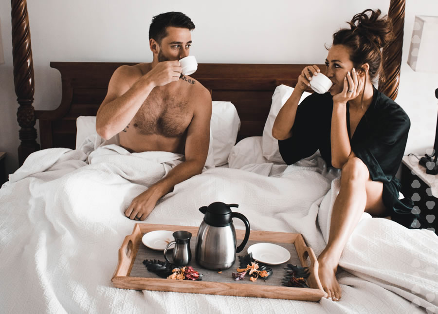 couple drinking coffee on a hotel bed.