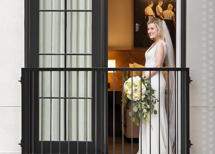 Bride standing in balcony of room at the Harpeth